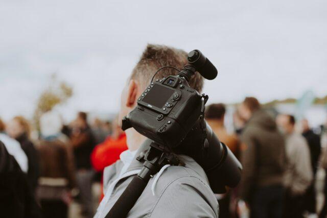 Videographer with DSLR and shotgun mic on monopod