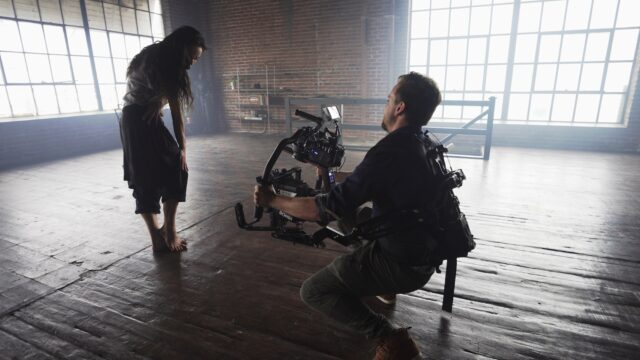 man with ronin 2 filming dancer in warehouse, coronavirus present implicitly