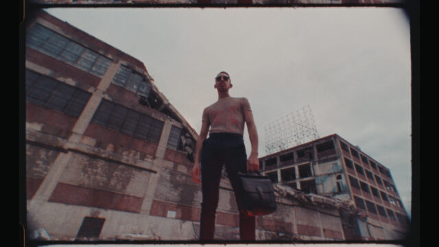 a film frame of a man standing in front of industrial buildings