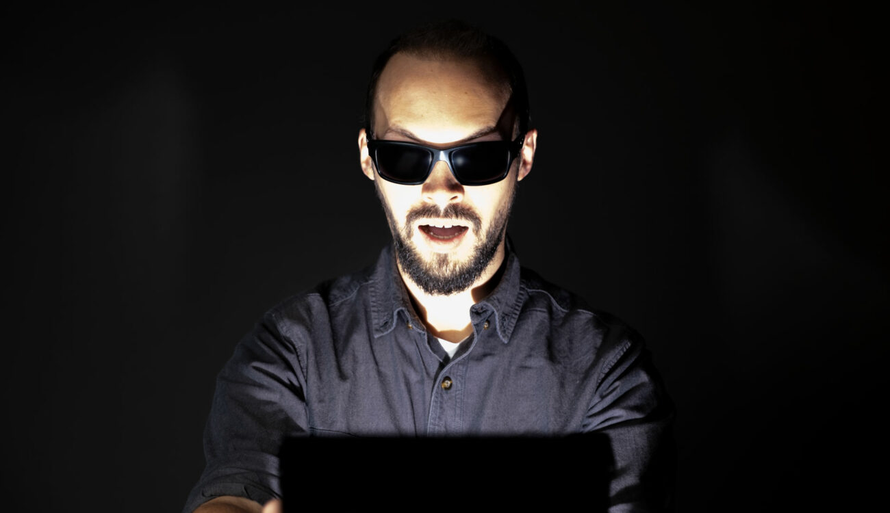 man with sunglasses blinded by monitor